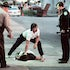 Shootout aftermath - Police officers watch as a paramedic checks for a pulse in a robbery suspect involved in a shootout with officers after a he crashed...
