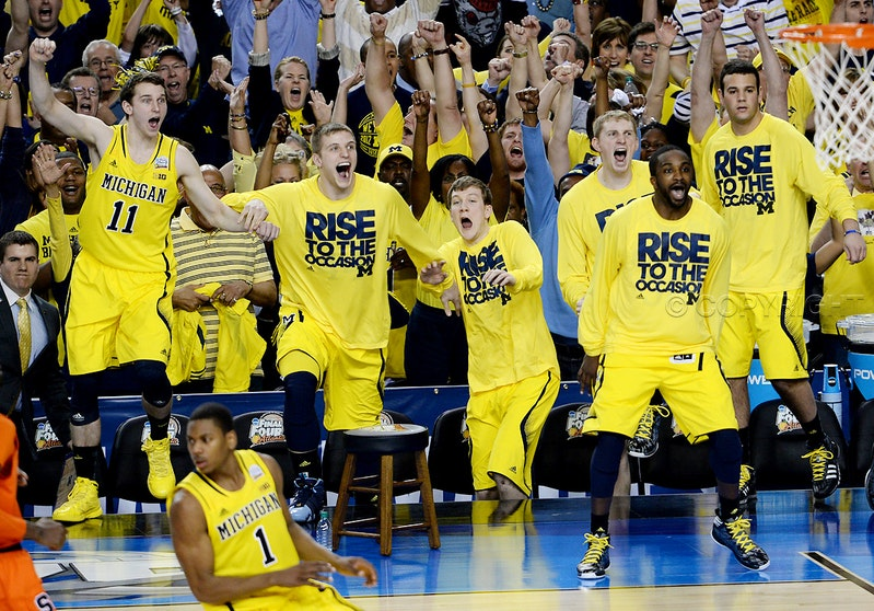 Fired up! - The Michigan bench celebrates in the closing moments of a 61-56 victory over Syracuse in an NCAA Final Four semifinal at the Georgia Dome in...