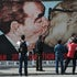 The kissing dictators - Tourists look at a painting on a remaining section of the Berlin Wall in Berlin, Germany. The painting is a copy of a famous photograph...