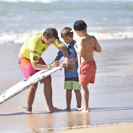 _XF22631 - 2015 12th February. Day 6 of the Australian Open of Surfing held at Manly Beach. Garrett Parkes (AUS) signs autographs for his young fans.