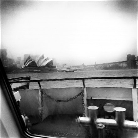 Through the Ferry Window,Opera House and The QE2 - Black and white photograph ,photographed in 1994 through the window of The Mosman ferry as the QE2 visits...