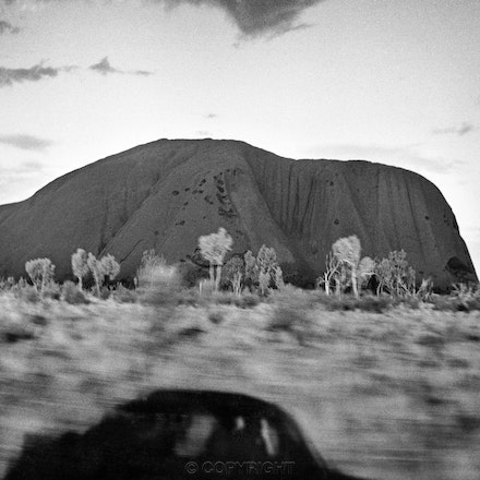 Uluru and Shadow - Photographed out the window in 1990 using a super wide angle lens of the iconic rock,with the shadow of the car giving a sense of movement...