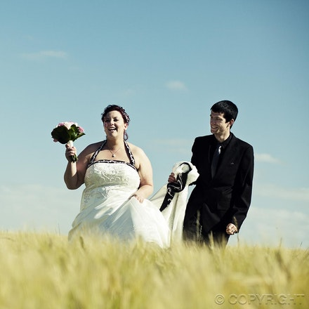 Simply Happy - A candid and happy moment as the bride and groom traverse the field