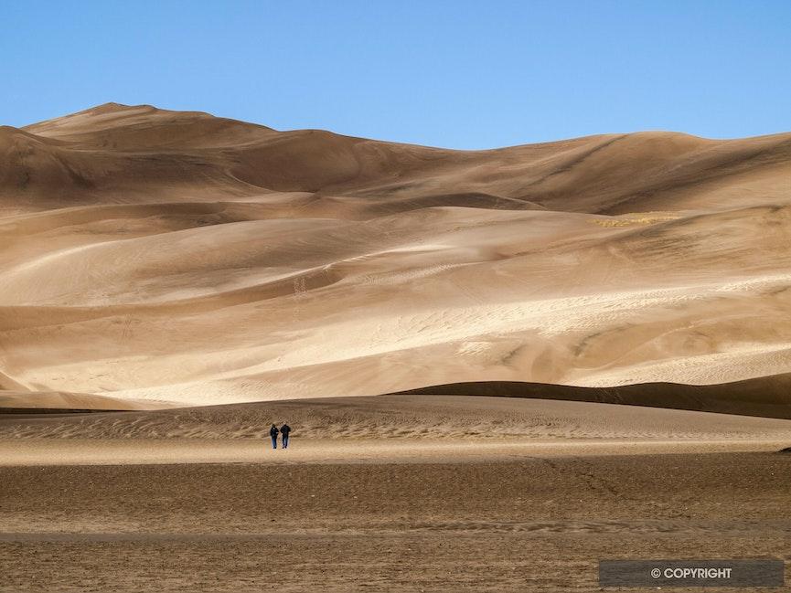 Hikers on sand dunes - GE Davis