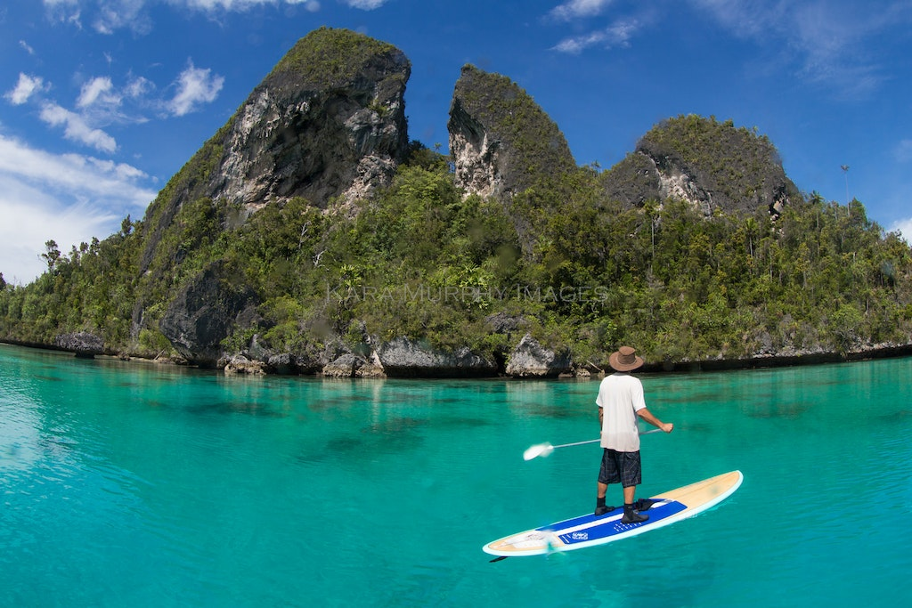 Wayag paddleboarding, Raja Ampat - Paddleboarding against the backdrop of Wayag Island's spectacular karst scenery, northwestern Raja Ampat.