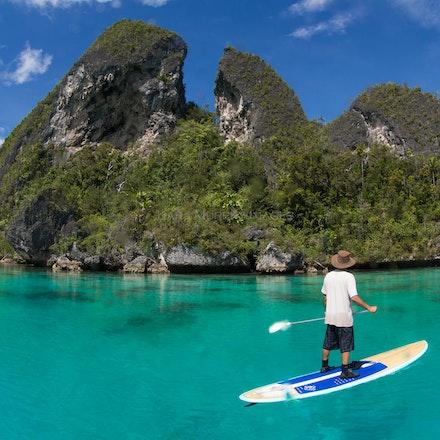 Wayag paddleboarding, Raja Ampat - Paddleboarding against the backdrop of Wayag Island's spectacular karst scenery, northwestern Raja Ampat.