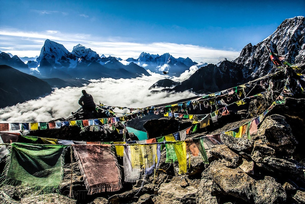 Gokyo Lakes, Nepal - Single male sitting on a rock on a peak above Gokyo Lake area, Nepal, with prayer flags flapping and a lake shrouded by low hanging...