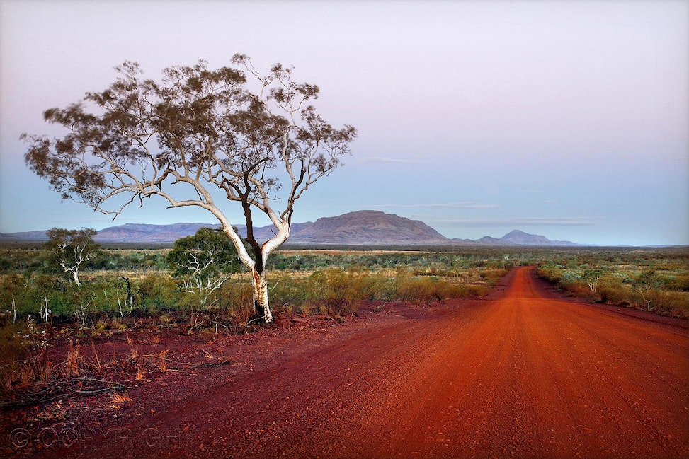 Sunset red road - Beautiful light on a red dirt road at sunset through Karijini National Park, Western Australia.