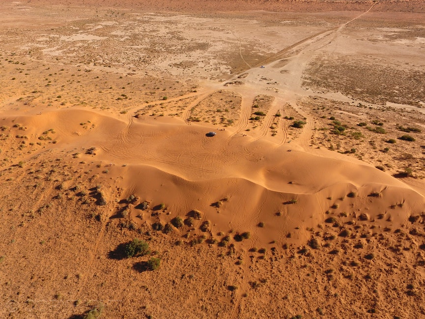 Big Red, Simpson Desert, Birdsville - Aerial drone view of Big Red sand dune with a four wheel drive on top, in the late afternoon light, Simpson Desert,...