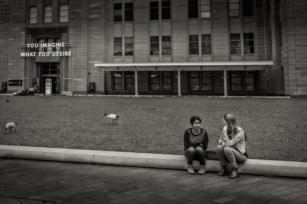 desire to imagine - a couple of young women sitting besides the museum of contemporary art in sydney, australia
