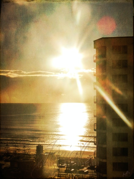 Sunrise over Highrise - The sun rises on a beach side Gold Coast apartment block. Textured for a vintage look.
