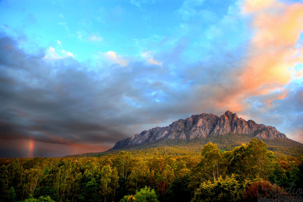 Mount Roland after the storm - A rainbow disappears into the distance in the wake of an afternoon storm over Mount Roland in Tasmania