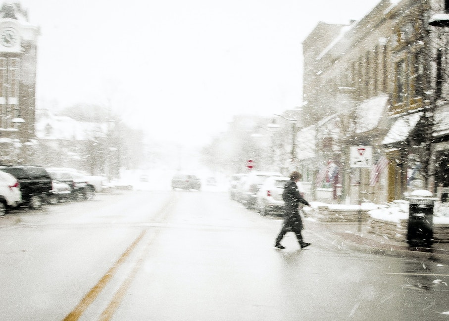 A Woman Walks In Winter - A woman walks across Washington Avenue, Grand Haven, Michigan, USA on a snowy day in January.