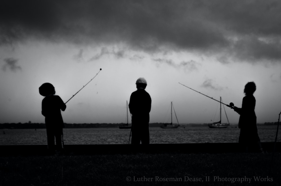 Fishing Awakens - Three young fishers gather poles beneath a slight flurry of rain.