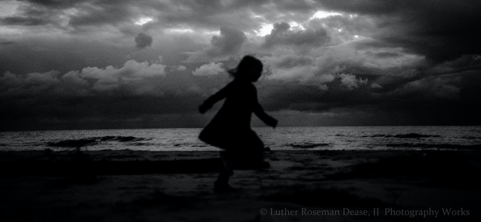 little girl - A little girl runs along the shoreline of Lake Michigan, at dusk in October.