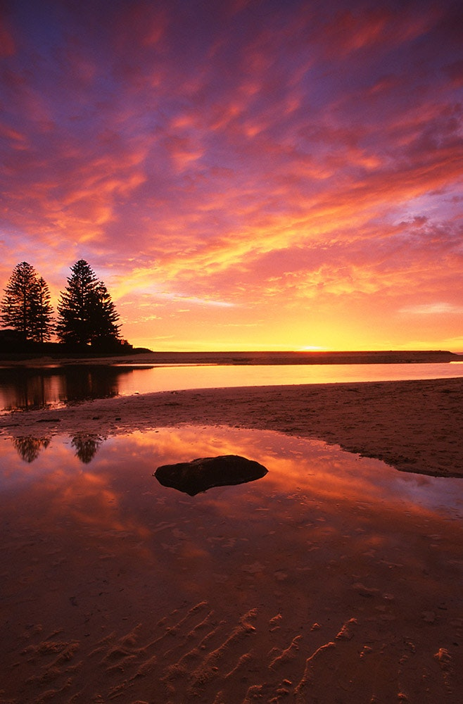 Skies Of Flame - One of the best sunrises I have ever seen, with its colours reflected in the still waters of Terrigal Lagoon. Taken in July 2003. (Image...
