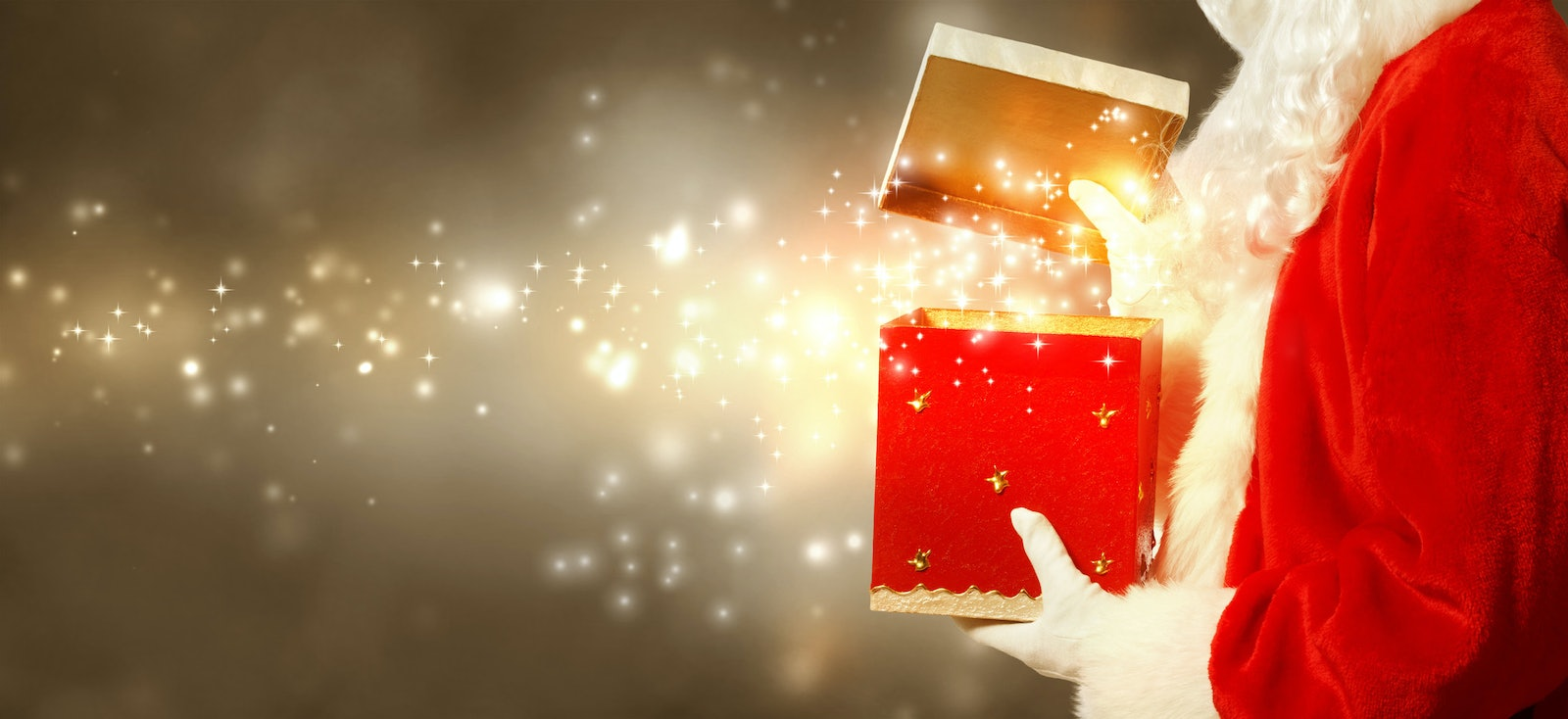 AdobeStock_94251896 - Santa Claus opening a red Christmas present on brown gold colored background