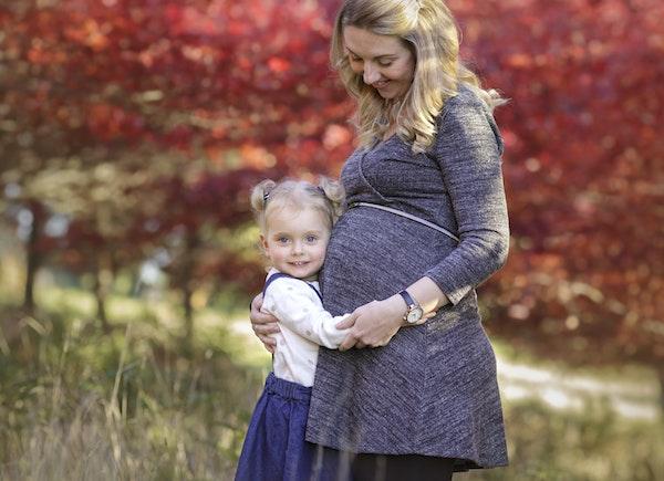daughter hugging mum pregnant belly