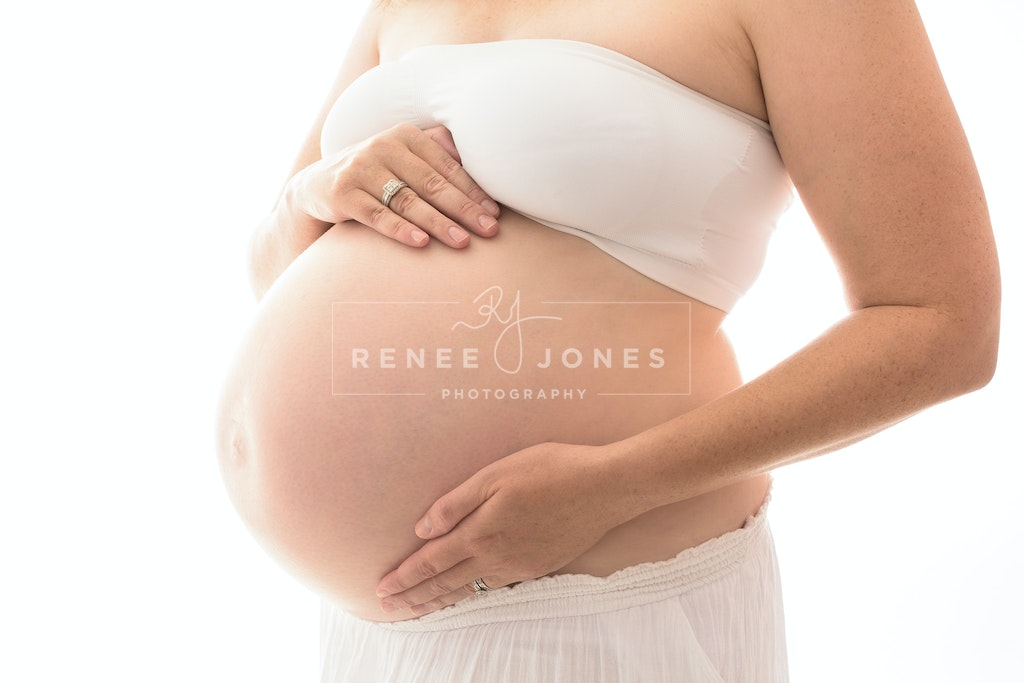 Beautiful Mumma - Soon to be Mother rests her hands on her beautiful baby belly