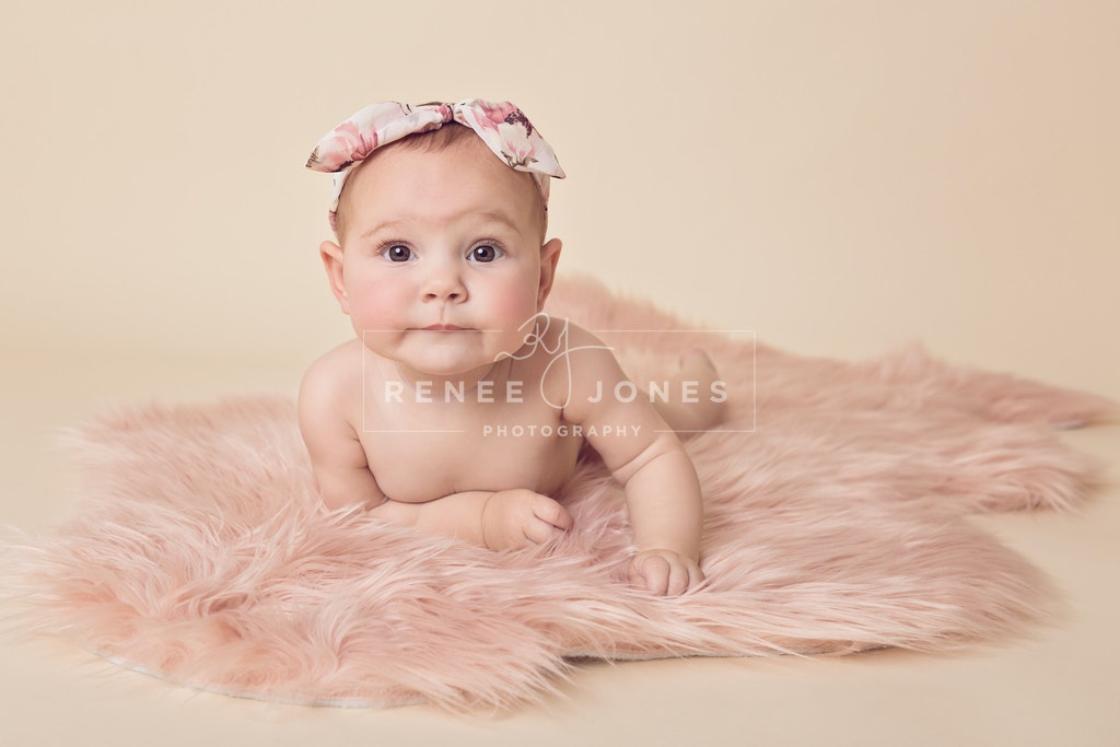 5 month milestone session - Baby girl laying on a pink fluffy rug with a cream background.