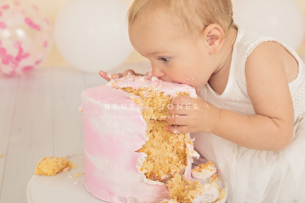 Delicious Cakes Supplied - Brisbane Cake Smash Photographer - Little girl enjoying eating her cake smash cake.