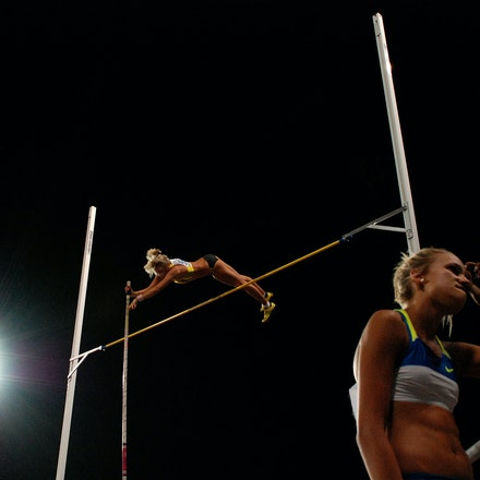 Sister act - Vicky Parnov clears the bar in the pole vault at the 2009 Australian Championships while younger sister Liz discusses her previous jump with...